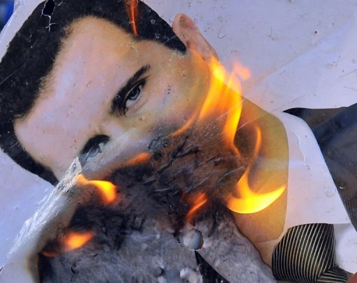 <p>A portrait of Syria President Bashar al-Assad is set alight on July 23 during clashes between rebel forces and the regime near Aleppo. The Syrian opposition would be willing to accept a transition led temporarily by a member of the regime if President Bashar al-Assad steps aside, the Syrian National Council said on Tuesday.</p>