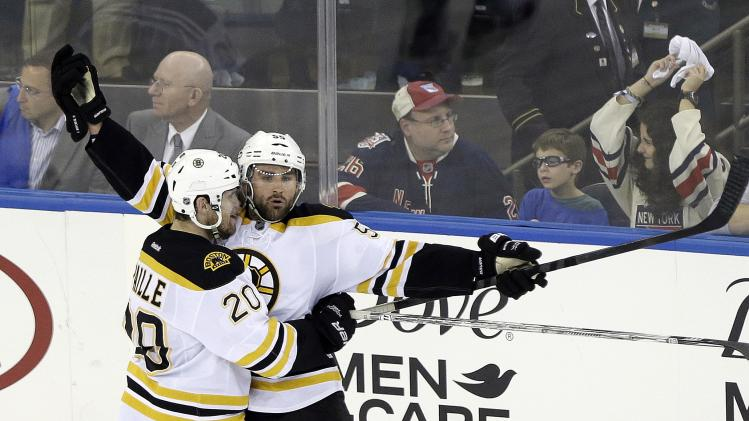 Boston Bruins' Johnny Boychuk, right, and Daniel Paille (20) celebrate a goal by Boychuk during the third period in Game 3 of the Eastern Conference semifinals in the NHL hockey Stanley Cup playoffs Tuesday, May 21, 2013, in New York. Paille later scored the game-winner. The Bruins won 2-1 and lead the best-of-seven games series 3-0. (AP Photo/Frank Franklin II)