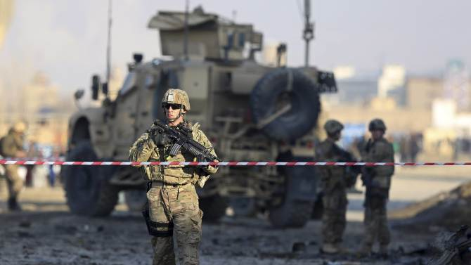 U.S. troops stand guard at the site of a suicide car bomb attack in Kabul