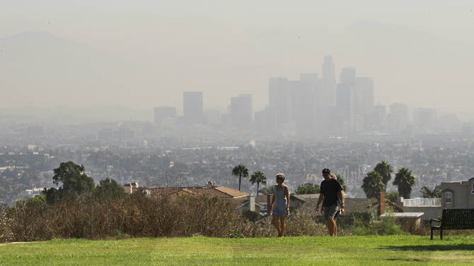On what would otherwise be a fairly clear day, the downtown Los Angeles skyline is obscured by smoke from wildfires in the Angeles National Forest, seen from the Baldwin Hills area of Los Angeles Tuesday, Sept. 4, 2012. It could be a week before firefighters can contain a the 3,600-acre blaze because of high temperatures and rugged terrain in thick brush that hasn't burned in a couple of decades. The cause of the fire that started Sunday afternoon in the San Gabriel Mountains, spoiling holiday hiking and camping plans for thousands, has not been determined. (AP Photo/Reed Saxon)