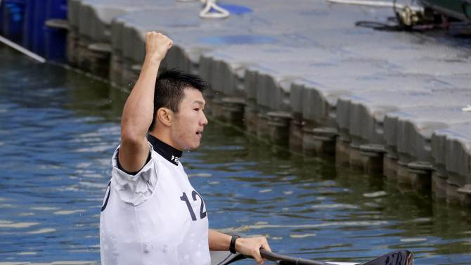 Japan's Kazuya Adachi raises his hand after defeating Tailand's Hung Ming Pan in the men's kayak single slalom final event at the Hanam Misari Canoe/Kayak Centre, during the 17th Asian Games in Incheon