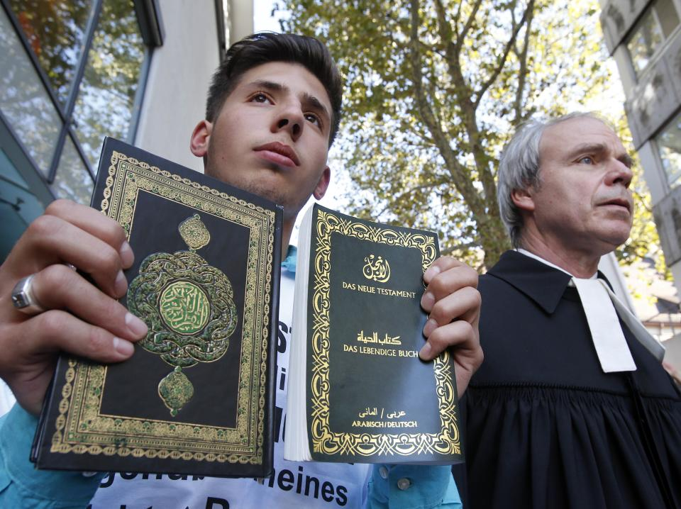 A young Muslim holding a Koran and a bible and a protestant priest demonstrate against an anti-Muslim film in downtown Freiburg, Germany, Friday, Sept. 21, 2012.  About 500 people took part in the first demonstration against the film in Germany.  (AP Photo/Michael Probst)