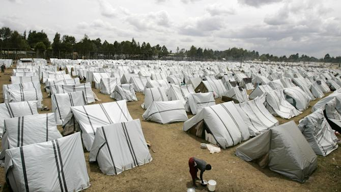 A file photo shows a woman cleaning utensils amid hundreds of tents set up for displaced people at the Eldoret Show Grounds