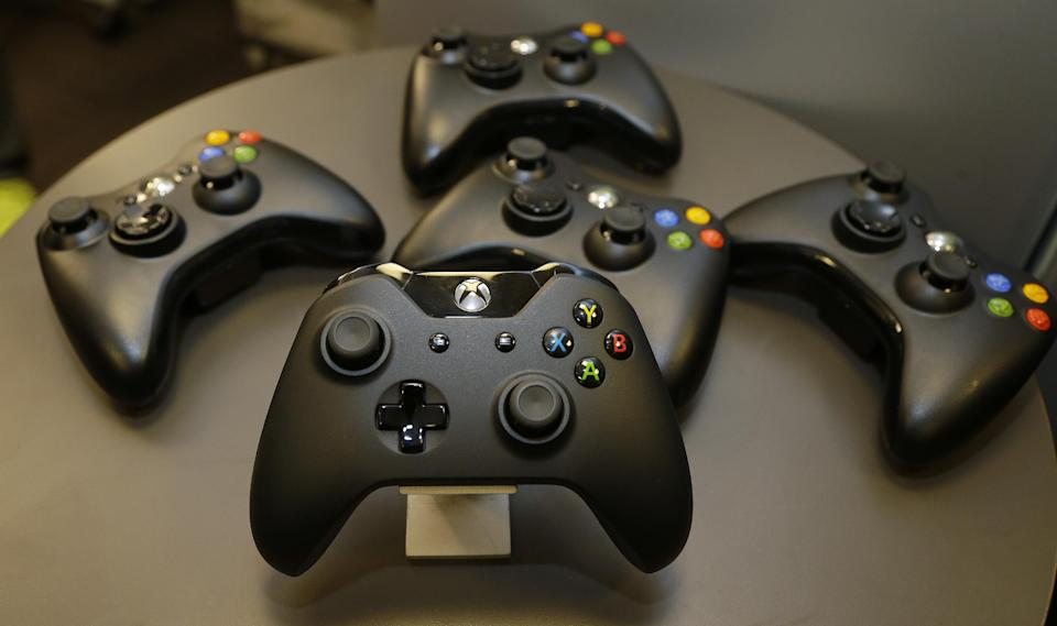 The new controller for Microsoft's next-generation Xbox One entertainment and gaming console system is shown front and center with older-generation controllers behind it, Tuesday, May 21, 2013, in Redmond, Wash. (AP Photo/Ted S. Warren)