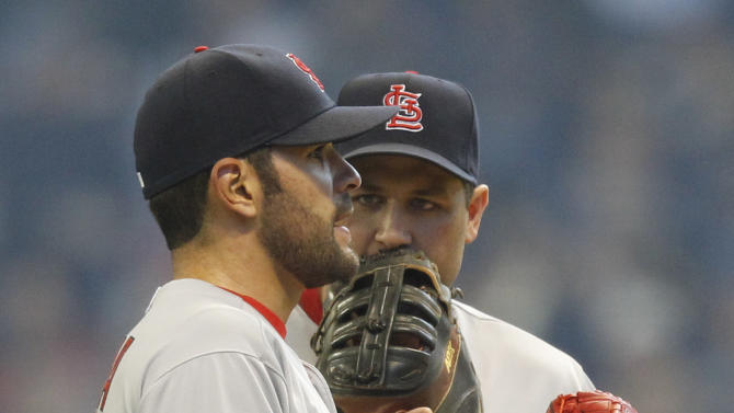 St. Louis Cardinals' Lance Berkman (12) talks to starting pitcher Jamie Garcia, left, during the first inning of an opening day baseball game against the Milwaukee Brewers, Friday, April 6, 2012, in Milwaukee. (AP Photo/Jeffrey Phelps)