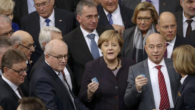 German Chancellor Angela Merkel holds her card before voting during a session of the German lower house of parliament, the Bundestag, in Berlin