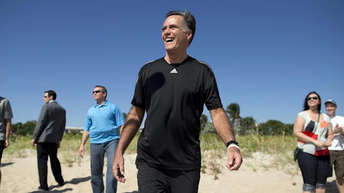 Republican presidential candidate, former Massachusetts Gov. Mitt Romney laughs as he watches a flag football game between between reporters that cover Romney, and Romney staff on Sunday, Oct. 21, 2012 in Delray Beach, Fla.  Romney took a short break from debate preparations to do the opening coin toss, and watch the first play of the game.  (AP Photo/ Evan Vucci)