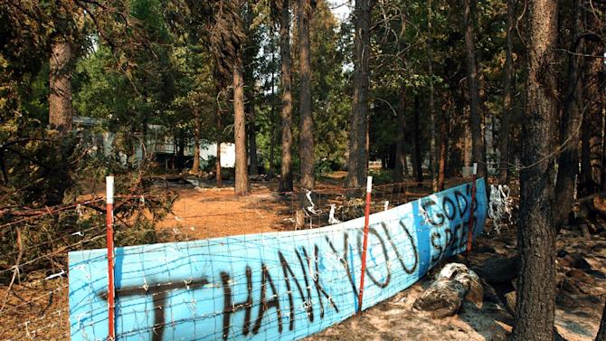 A sign with a message of thanks from a homeowner stands in front of a house that was saved by firefighters defending against a huge wildfire that has burned dozens of homes and other structures in remote, densely forested terrain through the hills outside Manton, Calif. The Ponderosa Fire, which has scorched about 38 square miles, was 50 percent contained Wednesday morning, according to the California Department of Forestry and Fire Protection. The threat to homes about 35 miles east of Redding has dropped from 3,500 earlier this week to roughly 200 residences. (AP Photo/Jeff Barnard)