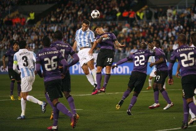 Malaga's Toulalan fights for a high ball against Porto's Otamendi during their Champions League soccer match in Malaga