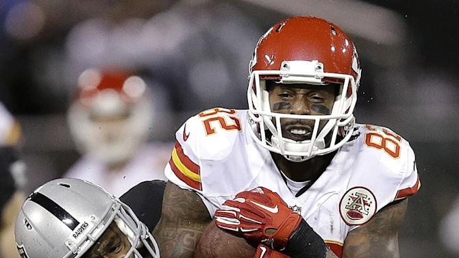 Kansas City Chiefs wide receiver Dwayne Bowe (82) is tackled by Oakland Raiders cornerback Brandian Ross (29) and defensive back Neiko Thorpe, right, during the fourth quarter of an NFL football game in Oakland, Calif., Thursday, Nov. 20, 2014