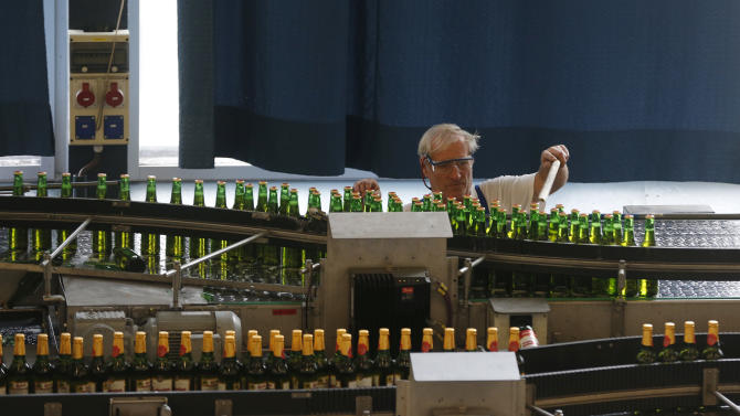 In this Tuesday, Oct. 30, 2012 photo a worker examines a line of bottles of beer, at the Budejovicky Budvar brewery, in Ceske Budejovice, Czech Republic. They've been arguing about a name for 106 years. A small brewer in the Czech Republic and the world's biggest beer maker have been suing each other over the right to put the word Budweiser on their bottles in what has become a David versus Goliath corporate saga. A deal, it seems, will have to wait a bit longer because settlement talks between state-owned Budejovicky Budvar and Anheuser-Busch, a U.S. company now part of AB InBev, have collapsed, according to Budvar's director general, Jiri Bocek. (AP Photo / Petr David Josek)