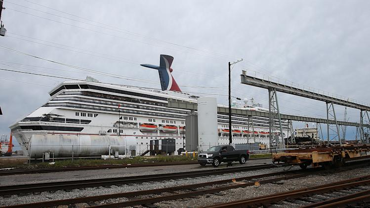 The Carnival cruise ship Triumph rests against a dock on the east side of the Mobile River after becoming dislodged from its mooring at BAE Shipyard during high winds Wednesday, April 3, 2013 in Mobile, Ala. Triumph was disabled Feb. 10 by an engine fire that stranded thousands of passengers onboard for days in the Gulf. It was towed into port in Mobile. (AP Photo/AL.com, Bill Starling)  MAGS OUT