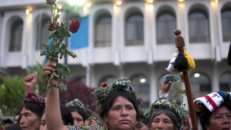 Ixil Indian women whose family members were killed in the country's civil war celebrate the judge's guilty verdict for Guatemala's former dictator Jose Efrain Rios Montt after his genocide trial in Guatemala City, Friday, May 10, 2013.  The baton at right represents the leadership of a local Ixil village.  The Guatemalan court convicted Rios Montt on charges of genocide and crimes against humanity, sentencing him to 80 years in prison. The 86-year-old former general is the first former Latin American leader ever found guilty of such a charge. The war between the government and leftist rebels cost more than 200,000 lives and ended in peace accords in 1996. (AP Photo/Luis Soto)