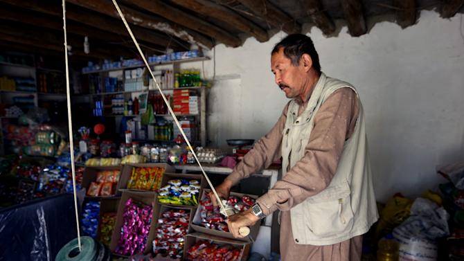 An Afghan shopkeeper exercises with a self made dumbbell at his shop in Kabul, Afghanistan, Tuesday, May 5, 2015. (AP Photo/Rahmat Gul)