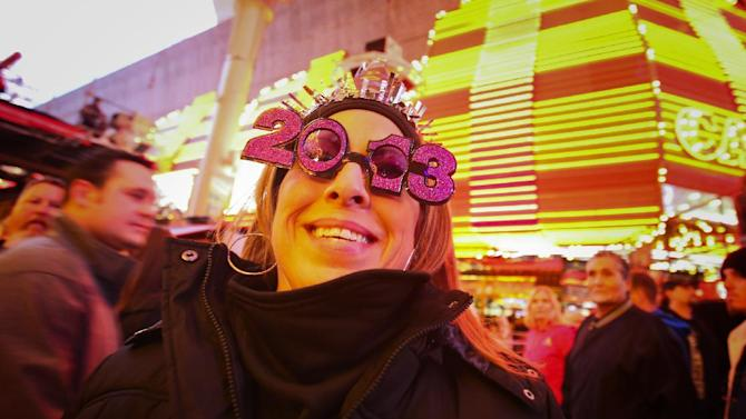 FILE - In this Monday, Dec. 31, 2012 file photo, Carmen Zepeda, of Corpus Christi, Texas, shows off her 2013 New Year's Eve glasses at the Fremont Street Experience Downtown Countdown in Las Vegas. On New Year's Eve night, some 340,000 people spending some $226 million, will crowd the Strip and downtown Fremont Street expecting to be entertained and for that reason, Las Vegas casino operators, event planners, tourism agencies and more have spent months planning ways to wow. (AP Photo/Las Vegas Review-Journal, Jeff Scheid, File)