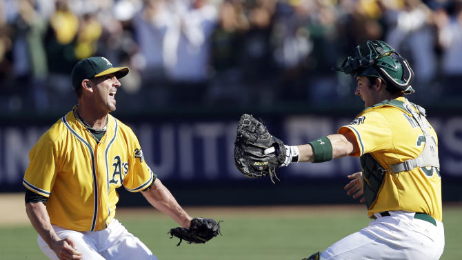 Oakland Athletics relief pitcher Grant Balfour, left, and catcher Derek Norris celebrate after their 12-5 win over the Texas Rangers in a baseball game, Wednesday, Oct. 3, 2012 in Oakland, Calif. The A's clinch the AL West title with the win. (AP Photo/Marcio Jose Sanchez)