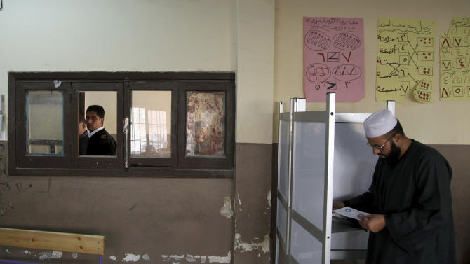 An Egyptian man casts his vote during a referendum on a disputed constitution drafted by Islamist supporters of President Morsi in Cairo, Egypt, Saturday, Dec. 15, 2012. (AP Photo/Khalil Hamra)