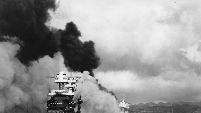 FILE - in this Dec. 7, 1941 file photo, the battleship USS West Virginia, center, begins to sink after suffering heavy damage, while the USS Maryland, left, is still afloat in Pearl Harbor, Oahu, Hawaii. The capsized USS Oklahoma is at right. (AP Photo/U.S. Navy, File)