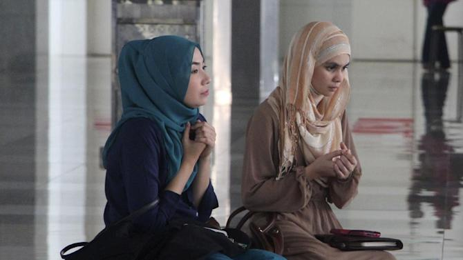 """CORRECTS CITY - Two women pray with others during a prayer session organized by former schoolmates of a cabin crew member of Malaysia Airlines Flight 17, which was shot down in Ukraine, at a mosque in Putrajaya, Malaysia Saturday, July 19, 2014. Malaysia's transport minister said the country is """"deeply concerned"""" that the site in Ukraine where the Malaysia Airlines jetliner was shot down with 298 people onboard """"has not been properly secured."""" (AP Photo/Satish Cheney)"""