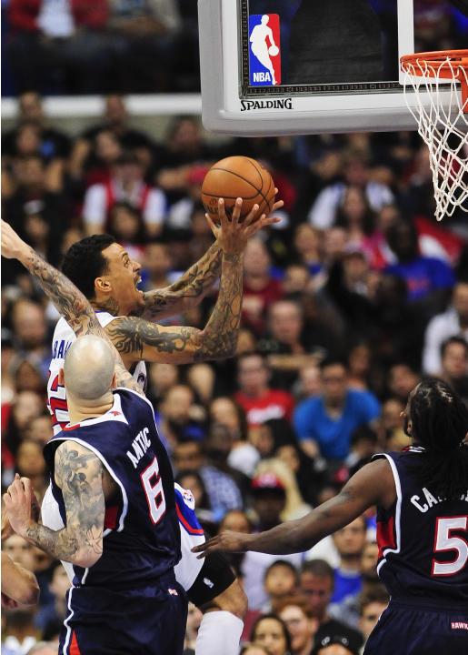 Los Angeles Clippers forward Matt Barnes, back left, drives to the basket past Atlanta Hawks center Pero Antic (6) and forward DeMarre Carroll (5) in the second half of an NBA basketball game, Saturda