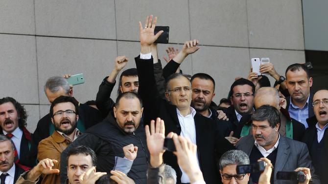 Zaman editor-in-chief Ekrem Dumanli greets his supporters after being released by the court outside the Justice Palace in Istanbul