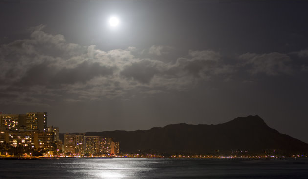 "A supermoon lights up Waikiki and Diamond Head Saturday, May 5, 2012, in Honolulu. A ""supermoon"" event happens when the moon is closest to the earth therefore the biggest and brightest full moon of th"