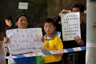 Petitioners hold banners on Saturday outside the hopital where Chinese activist Chen Guangcheng is staying. Chen Guangcheng says he remains in a Beijing hospital but has asked government officials to help him apply to go abroad, after a deal between China and the United States