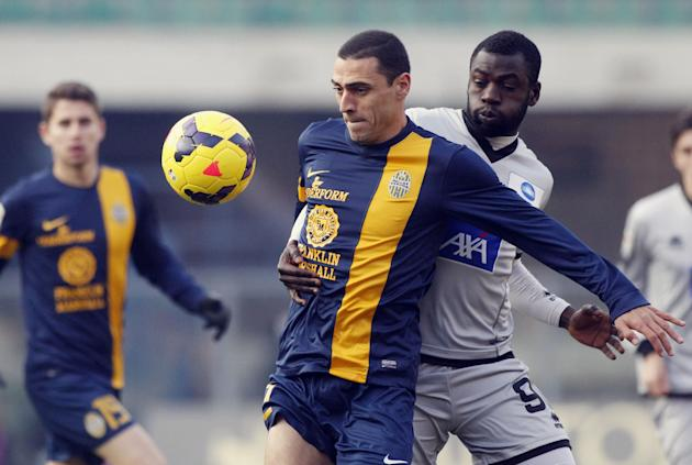 Atalanta's Moussa Kone, right, of Ivory Coast, challenges Hellas Verona Brazilian midfielder Romulo during a Serie A soccer match at Bentegodi stadium in Verona, Italy, Sunday, Dec. 8, 2013