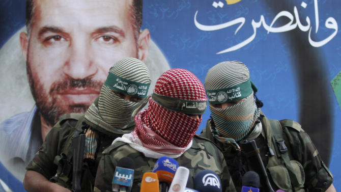 """A Hamas militant talks during a press conference in Gaza City, Thursday, Nov. 22, 2012. Gazans are celebrating a cease-fire agreement reached with Israel to end eight days of the fiercest fighting in nearly four years constricting the Gaza Strip. The poster behind him reads: """"Gaza won"""" and shows the picture of Ahmed Jabari,a Hamas leader assassinated on Nov.14, setting off the last round of fighting between Israel and Hamas . (AP Photo/Hatem Moussa)"""
