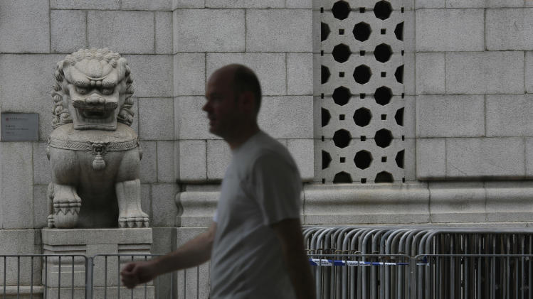 A man walks past some iron barriers which are prepared for the possible protest at the financial Central district in Hong Kong Sunday, Aug. 31, 2014. China's legislature on Sunday ruled against allowing open nominations in elections for Hong Kong's chief executive, a decision that promises to ignite political tensions in the Asian financial hub. Hong Kong democracy activists have held massive protests demanding that Chinese leaders let the city's voters choose their chief executive from an open list of candidates.(AP Photo/Vincent Yu)