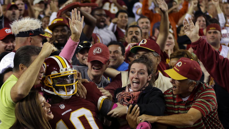 Washington Redskins quarterback Robert Griffin III (10) celebrates with the fans after a 76-yard touchdown run during the second half of an NFL football game against the Minnesota Vikings, Sunday, Oct. 14, 2012, in Landover, Md. (AP Photo/Pablo Martinez Monsivais)