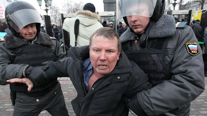 Russian police officers detain protester after a rally in Moscow, Russia, Monday, March 5, 2012. Riot police on Monday broke up an opposition protest contesting Prime Minister Vladimir Putin's victory in Russia's presidential election, arresting dozens of participants, including prominent opposition leaders. The police action followed a rally in downtown Moscow that drew about 20,000 protesters angry over a campaign slanted in Putin's favor and reports of widespread violations in Sunday's ballot. (AP Photo/Yuri Tutov)