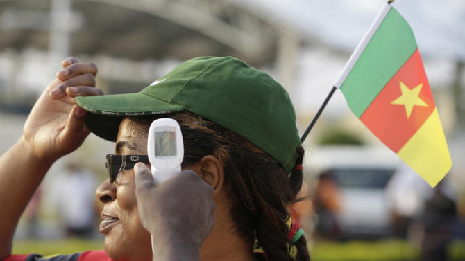 A health worker takes the temperature of a Cameroon soccer supporter  before their African Cup of Nations Group D soccer match  at Estadio De Malabo in Malabo, Equatorial Guinea, Wednesday, Jan. 28, 2015. (AP Photo/Sunday Alamba)