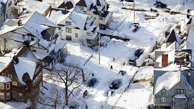 Pedestrians walk along a snow clogged street in Southwestern Connecticut, Sunday, Feb. 10, 2013, in the aftermath of a storm that hit the region and much of the New England states. (AP Photo/Craig Ruttle)