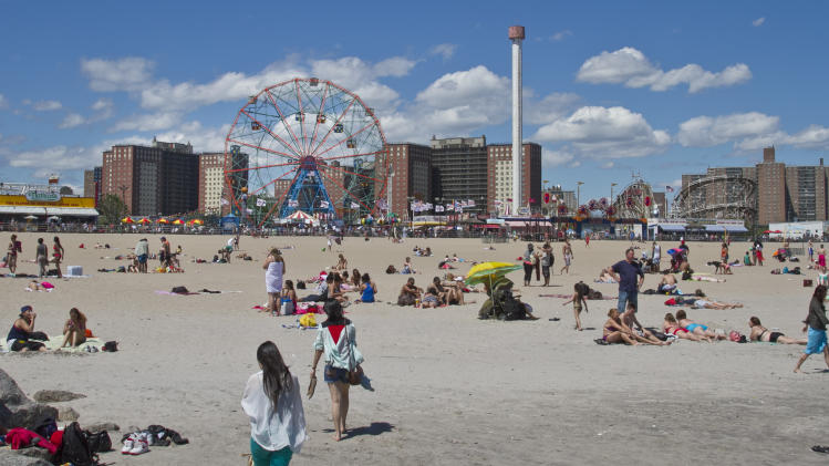This June 12, 2013 photo shows the Wonder Wheel along the Coney Island boardwalk while visitors take to the beach in the Brooklyn borough of New York. (AP Photo/Bebeto Matthews)