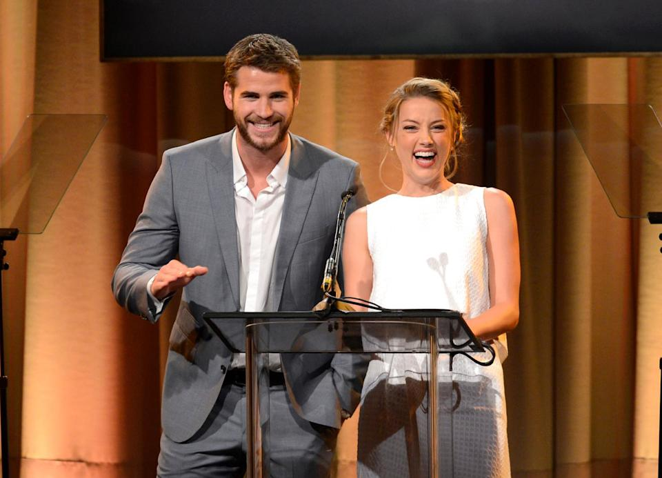Liam Hemsworth, left, and Amber Heard speak on stage at the Hollywood Foreign Press Association Luncheon at the Beverly Hilton Hotel on Tuesday, Aug. 13, 2013, in Beverly Hills, Calif. (Photo by Chris Pizzello/Invision/AP)