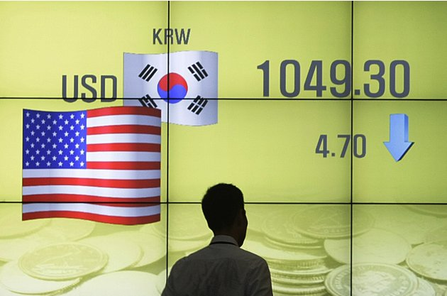 A man walks past a screen showing the exchange rate between the U.S. dollar and the South Korean won in Seoul, South Korea, Monday, Aug. 1, 2011. South Korean stocks rose 39.1 points, or 1.83 percent