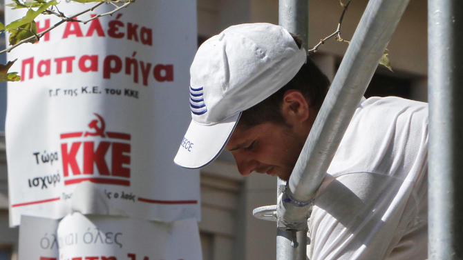 A worker places posters for an elections rally of the New Democracy party, with a Greek flag, the radical left-wing Syriza party and Communistic KKE party, at Syntagma square in central Athens, Thursday, June 14, 2012. Greece faces crucial national elections on Sunday, that could ultimately determine whether the debt-saddled, recession bound country remains in the eurozone. (AP Photo/Petros Karadjias)
