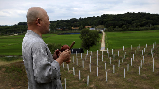"In this Thursday, June 28, 2012 photo, Mukgai, a South Korean who goes by his Buddhist name and plans to become a monk, offers a prayer for hundreds of North Korean and Chinese soldiers who died in the Korean War and are buried at the ""enemy cemetery,"" just south of the Demilitarized Zone in Paju, South Korea. (AP Photo/Hye Soo Nah)"