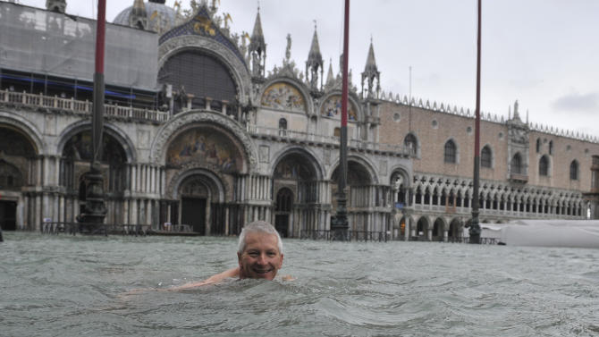 A man enjoys swimming in flooded St. Mark's Square in Venice, Italy, Sunday, Nov. 11, 2012. High tides have flooded Venice, leading Venetians and tourists to don high boots and use wooden walkways to cross St. Mark's Square and other areas under water. Flooding is common this time of year and Sunday's level that reached a peak of 58.66 inches (149 centimeters) was below the 63 inches (160 centimeters) recorded four years ago in the worst flooding in decades. (AP Photo/Luigi Costantini)