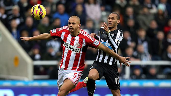 Sunderland's Wes Brown, left, vies for the ball with Newcastle United's Yoan Gouffran, right, during the English Premier League soccer match between Newcastle United and Sunderland,  at St James' Park, Newcastle, England, Sunday, Dec. 21, 2014. (AP Photo/Scott Heppell)