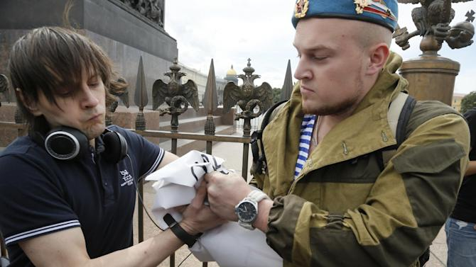 A former paratrooper celebrating Paratroopers Day, right, takes away a broadsheet of a gay rights activist who is taking part in a protest at Dvortsovaya (Palace) Square in St.Petersburg, Russia, Sunday, Aug. 2, 2015. Several gay rights activists stood protesting against gay rights violation at Palace square where paratroopers celebrated Paratroopers' Day. Paratroopers are an elite unit of the Russian Army, and everyone in the country recognize their blue berets.(AP Photo/Dmitry Lovetsky)