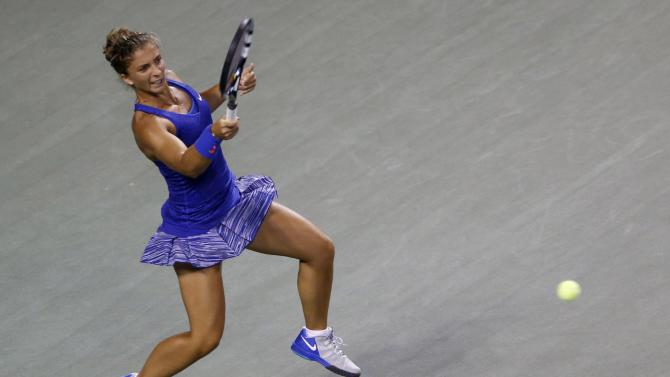 Errani of Italy returns a shot to Erakovic of New Zealand during their Pan Pacific Open women's singles tennis match in Tokyo