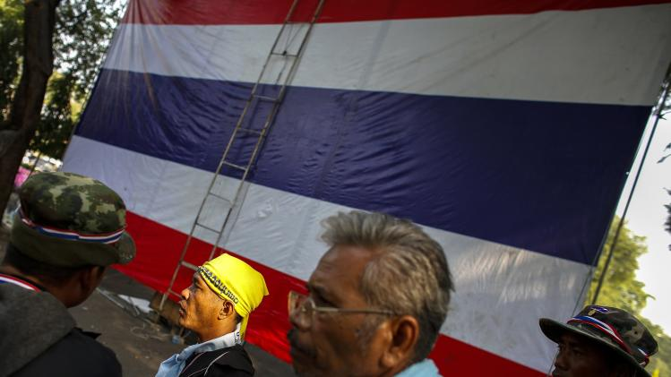 Anti-government protesters gather near a big Thai national flag in Bangkok