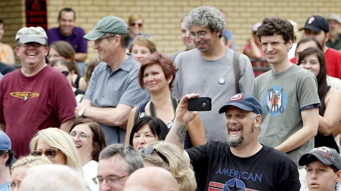 Audience members laugh while listening to a speech during the unveiling of an Atheist monument outside the Bradford County Courthouse on Saturday, June 29, 2013 in Stark, Fla. The New Jersey-based group American Atheists unveiled the 1,500-bound granite bench Saturday as a counter to the religious monument in what's called a free speech zone. Group leaders say they believe it's the first such atheist monument on government property. About 200 people attended the event. (AP Photo/The Gainesville Sun, Matt Stamey)