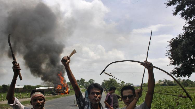 Demonstrators with their weapons shout slogans during a protest at Golaghat district in Assam