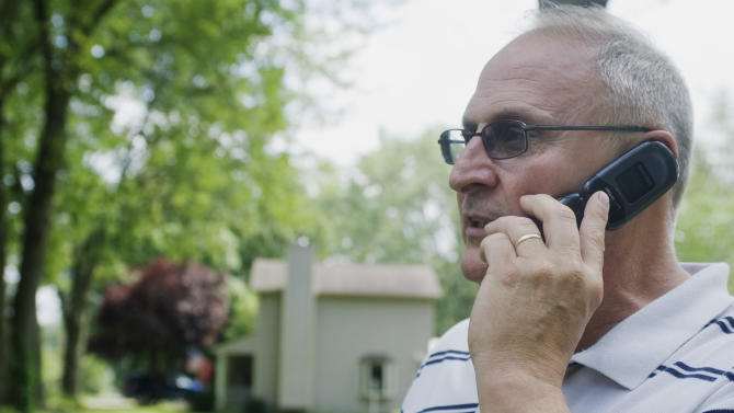 Bill Stinnett, assures his daughter on his phone that he is ok, at his home, about a block away from a multiple death shooting in Copley Twp. a suburb of Akron, Ohio, Sunday, Aug. 7. 2011. A family argument in the Akron suburb ended in the shooting deaths of eight people in two places, including an 11-year-old, and two more people were wounded, authorities said Sunday  (AP Photo/Phil Long)