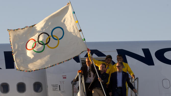 Rio de Janeiro's Mayor Eduardo Paes, front left, holds up the Olympic flag upon its arrival in Rio de Janeiro, Brazil, Monday, Aug. 13, 2012. The flag's arrival marks the official start of Rio's Olympic preparations, with the city to undertake nearly 200 projects to construct sports venues and other infrastructure during the next four years. At right, front, Carlos Arthur Nuzman, President of the Brazilian Olympic Committee. (AP Photo/Silvia Izquierdo)