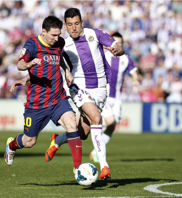 Barcelona's Messi and Valladolid's Rueda fight for the ball during their Spanish first division soccer match in Valladolid