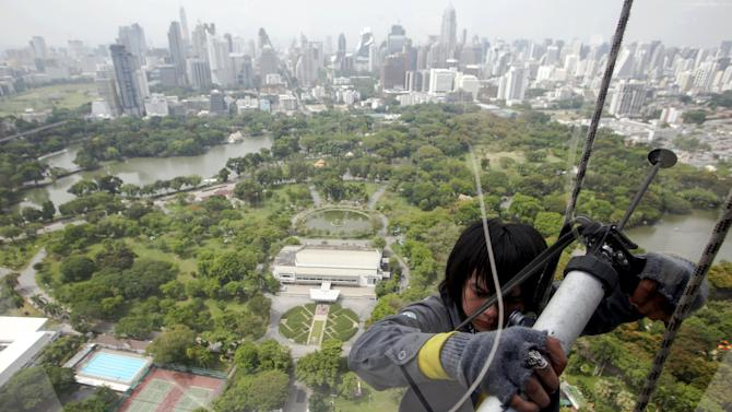 A man works on a high-rise building while suspended on ropes in Bangkok